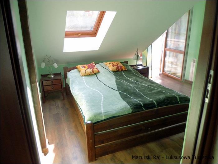 Sypialnia z łóżkiem małżeńskim i z pieknym widokiem na jezioro i las